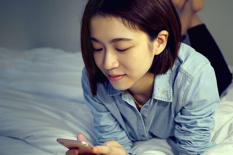 persona con teléfono en la cama