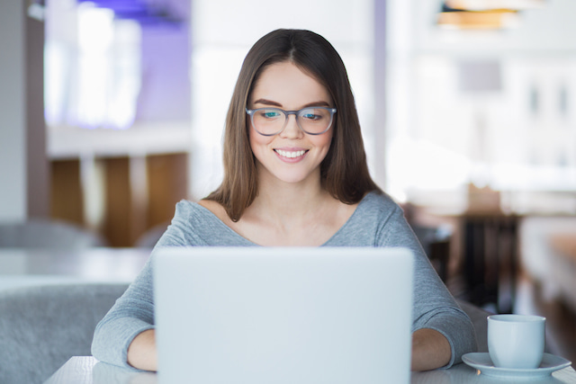 woman wearing blue light glasses while working on a computer to be productive.