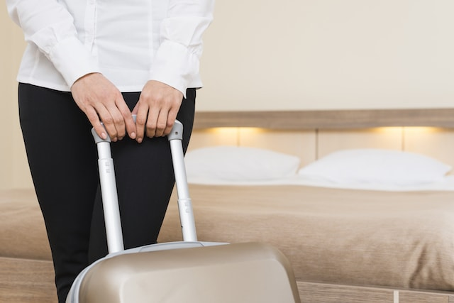 A woman holding a suitcase inside a hotel room.