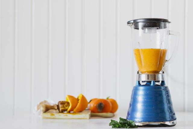 a blender with an orange smoothie inside.