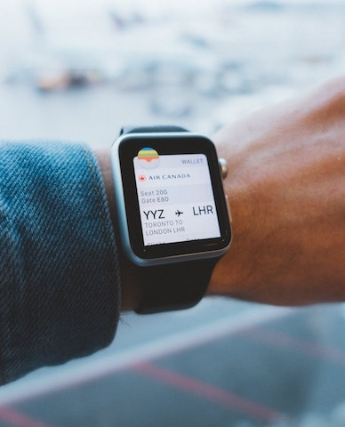An apple watch showing a boarding pass with personal information.