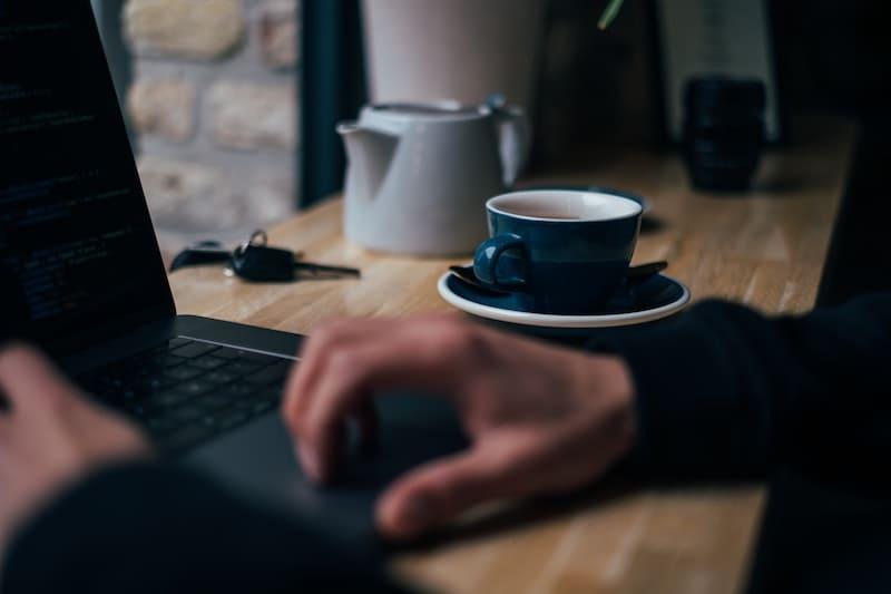 persona usando el ordenador mientras toma café