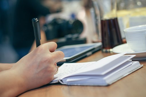 Persona escribiendo en una libreta.