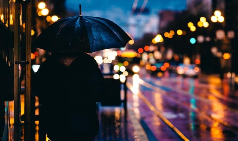 Hombre con paraguas de noche